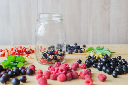 Red, white, black currant, red and black raspberries, white strawberries and mint leaves with glass jar on wooden table as ingredient to healthy cocktail, beverage, yogurt, smoothie