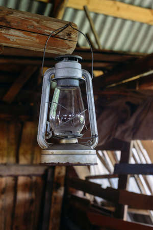 oil lamp: The old rusty kerosene lamp hangs on the nail in a half-ruined wooden building