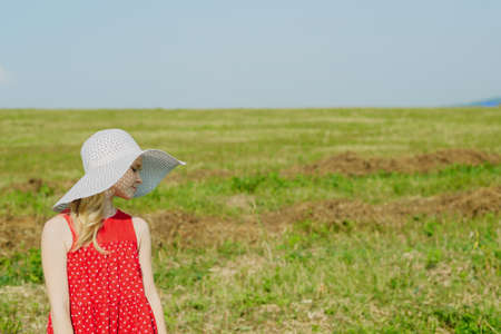 girl in red dress and white hat with large brim going on road in field