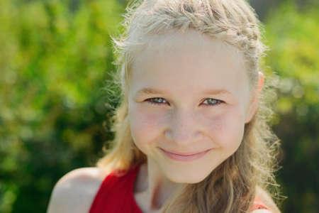 portrait of cute little blonde caucasian girl on green grass background