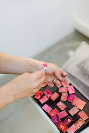 Stylist pick color of lipstick on his hand, stock photo image