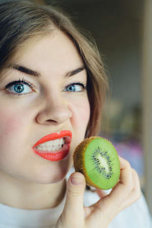 portrait of blonde young woman with sliced kiwi fruit, parody of beautiful glamorous girls or allergy concept, stock photo image