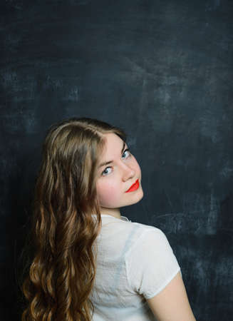 headshot portrait of young adult caucasian woman on black school blackboard in white blouse, stock photo image background blouse