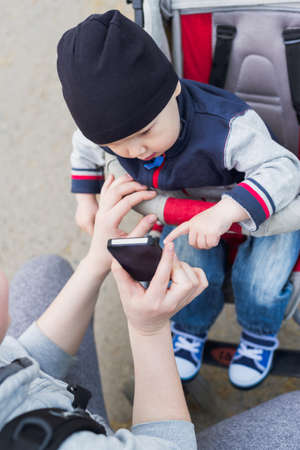 Baby boy in sitting stroller touching mobile smart phone in moms hand, lifestyle stock photo image