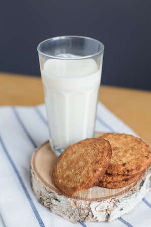 still life of round brown wholegrain flour cookies and milk glass on striped white napkin on wooden table, angle above view of vertical stock photo image
