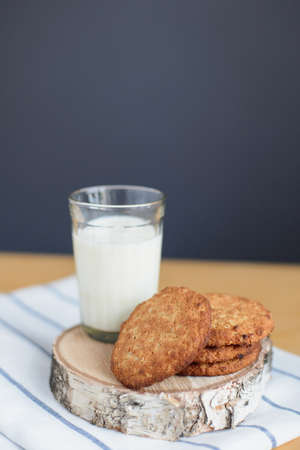 still life of round brown wholegrain flour cookies and milk glass on striped white napkin on wooden table, side view of vertical stock photo image with copy space for text