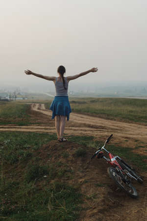 white european young woman stand in village hill road with bike, keep hands to side, look at open space, view from back in full body size, vertical lifestyles stock photo image 版權商用圖片
