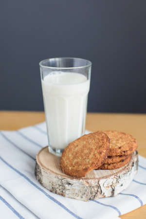 still life of round brown wholegrain flour cookies and milk glass on striped white napkin on wooden table, side view of vertical stock photo image Stock Photo