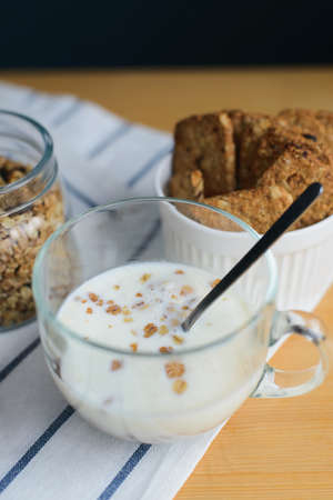 milk and cereals flakes in glass cup with granola and wholegrain cookies on striped textile napkin on wooden table, close up view from angle above of vertical still life stock photo image