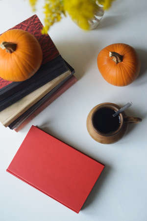 autumn flat lay still life with books stacked, orange pumpkins, clay drinking cup with spoon, top view of vertical stock photo image mockup
