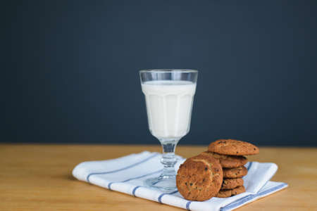 round brown wholemeal oatmeal cookies stack with raisins and white milk in glass cup on striped textile cloth on wooden table, close up side view of vertical still life stock photo image