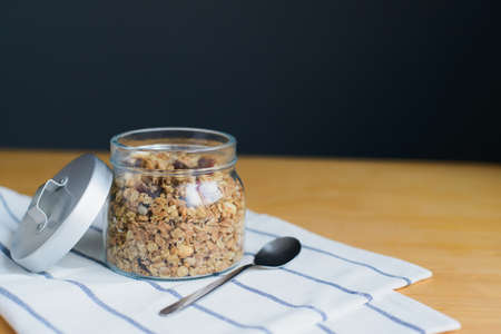 baked muesli with peanuts, hazelnuts, oat and wheat flakes in glass bowl on striped textile napkin on wooden table, close up top view of horizontal still life stock photo image