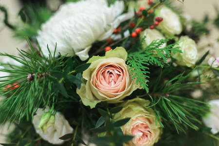 close up winter bridal bouquet with white bush roses, chrysanthemum, pine, thuja, ilex, pistachio, side view of horizontal stock photo image