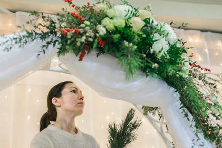 caucasian women florist worker make winter wedding bouquet arch composition with roses, eustoma, chrysanthemum, pine, waxflower, ilex, pistachio, thuja, view from below of horizontal stock photo image