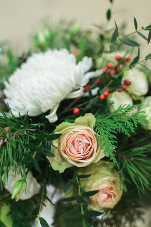 close up winter bridal bouquet with white roses, chrysanthemum, pine, thuja, ilex, pistachio, above side view of stock photo image Stock Photo