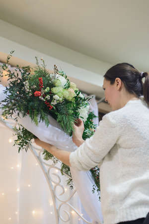 white caucasian women florist worker make winter wedding bouquet arch composition with roses, eustoma, chrysanthemum, pine, waxflower, ilex, pistachio, thuja, side view of vertical stock photo image Stock Photo