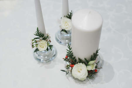 white thick and thin candles in glass candlestick with rose, ilex, thuja, eustoma, waxflower, eucalyptus bouquet composition on table for winter wedding decor, horizontal stock still life photo image Banque d'images
