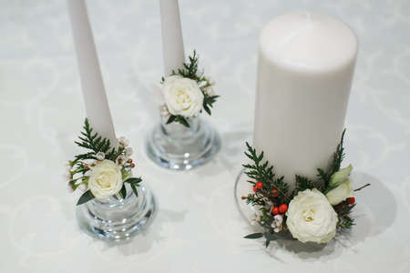 white thick and thin candles in glass candlestick with rose, ilex, thuja, eustoma, waxflower, eucalyptus bouquet composition on table for winter wedding decor, horizontal stock still life photo image