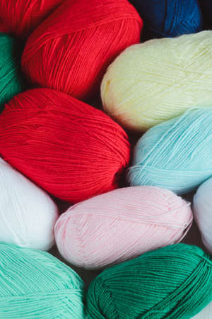 close-up colorful oval acrylic colorful wool yarn thread skeins background, view from above, flat lay, vertical stock photo image