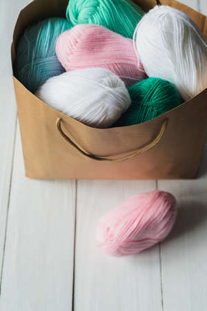 oval acrylic colorful wool yarn thread skeins lying near and into kraft paper brown package on white wooden boards background, view from angle above, vertical stock photo image