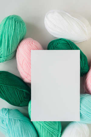white paper sheet on acrylic soft pastel colored wool yarn thread skeins heap on white background, top view flat lay vertical stock photo image mockup with copy space for text 写真素材