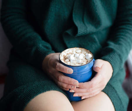 white caucasian woman in green knitted cardigan holding blue cup with cacao and marshmallow, front view, vertical stock photo image