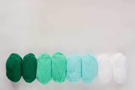 acrylic soft pastel green and white colored wool yarn thread skeins row on white background, top view flat lay horizontal stock photo image mockup with copy space for text 版權商用圖片