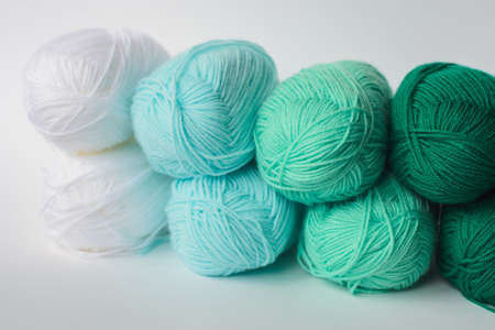 acrylic soft pastel green, azure and white colored wool yarn thread skeins row on white background, side view, horizontal stock photo image background with copy space for text