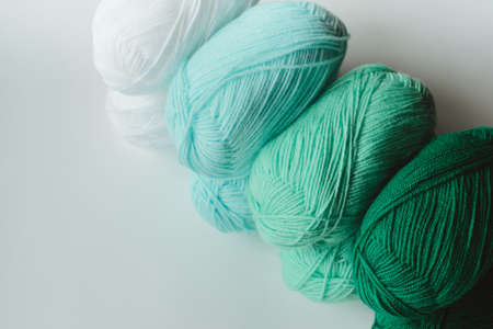 acrylic soft pastel green, azure and white colored wool yarn thread skeins row on white background, top angle view, horizontal stock photo image with copy space for text