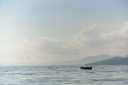 wooden boat with no people in bay sea with sky and mountain background, horizontal stock photo image backdrop Standard-Bild