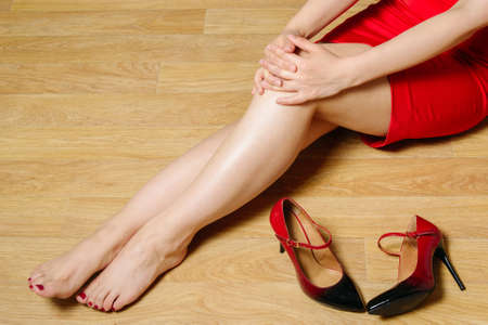 white caucasian woman in short red dress sit on floor without high-heeled shoes fold your hands on knee, horizontal indoors stock photo image