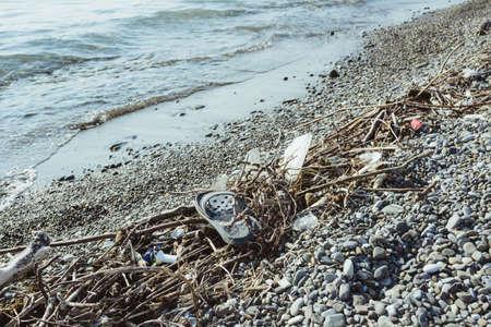 garbage, junk, litter, broken tree branches on pebble shore sea beach, environmental protection concept, horizontal lifestyle stock photo image photography background Standard-Bild