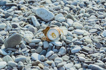 crumpled aluminum metal orange can on pebble beach, environmental protection concept, horizontal lifestyle stock photo image background Standard-Bild