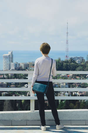 young woman tourist in full growth stands on observation deck and looks at city, sea and sky, back view, vertical outdoors lifestyle stock photo image