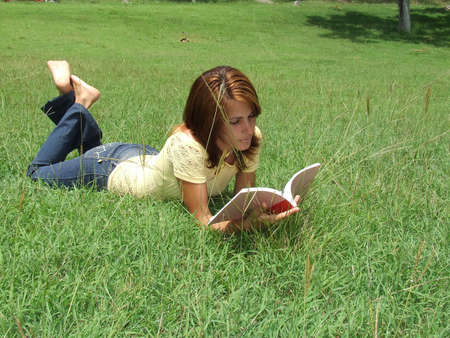 Beautiful girl reading a book while laying on the grass photo