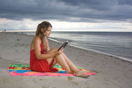 Girl with red dress reading a book in the beach, sitting on a towel