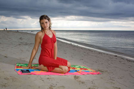 Girl with red dress on a towel, in the beach photo