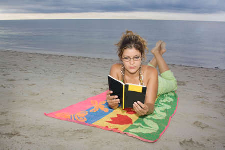 Girl with glasses reading a book in the beach, laying on a towel photo