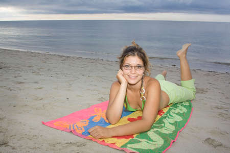 Beautiful lady smiling in the beach, laying on a coloured towel (I) photo