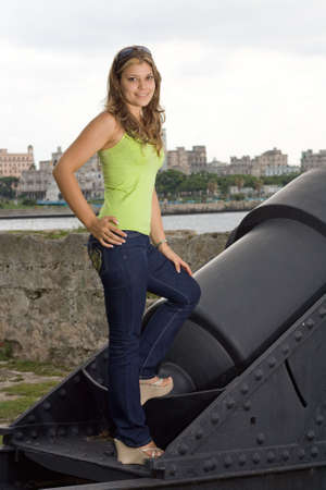 angelical: Beautiful lady smiling and standing on an old cannon, with Havana view background