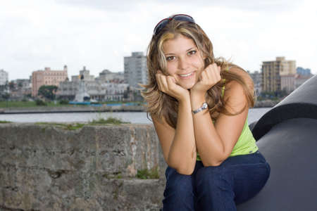 angelical: Beautiful lady smiling and siiting on an old cannon, with Havana view background Stock Photo