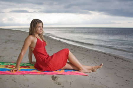 Attractive girl sitting on a towel, looking to the sea at sunset photo