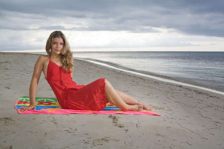 Attractive girl sitting on a towel, with red dress at beach sunset photo