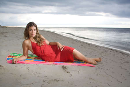 Attractive girl laying on a towel with red dress, at beach sunset photo