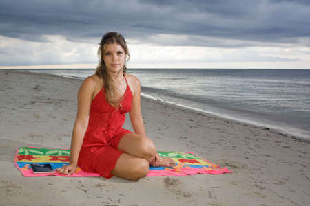 Attractive girl with red dress sitting beside a book, at beach sunset photo