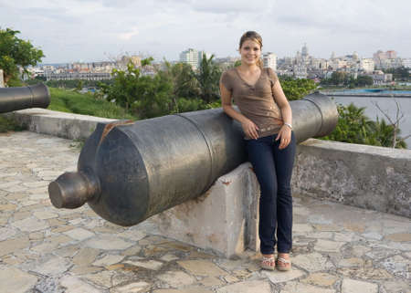 angelical: Girl standing beside a cannon with Havana City in the backgroud Stock Photo