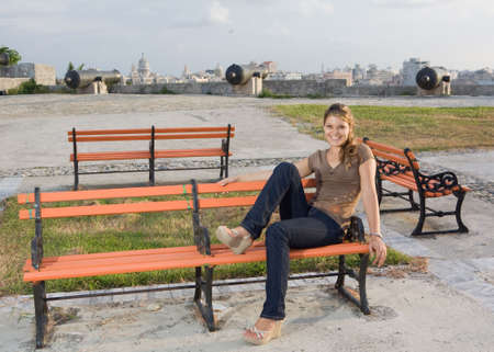 angelical: Girl relaxing in a orange coloured bench, in a park Stock Photo