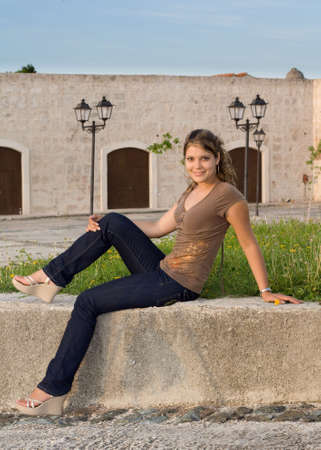 angelical: Girl with blue jeans sitting and relaxing on a stone bench Stock Photo