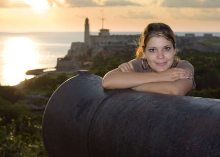 angelical: Beautiful girl smiling near an old cannon, with Morro lighthouse in the background Stock Photo
