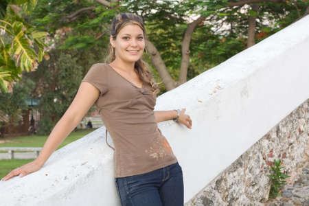 angelical: Girl relaxing and smiling in a white painted stone fence